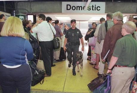 A security officer walks with his bomb detection K-9 through a crowd of waiting passengers in the American Airlines terminal area at Boston's Logan International Airport, Monday, Sept. 17, 2001. (AP Photo/Bizuayehu Tesfaye) Published in NYT 09/21/01 Published caption: A security officer roamed among waiting passengers this week at Logan International Airport in Boston. (Associated Press) 10logan airlinegallery
